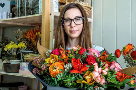 Female florist in flower shop. Woman holding in hands a beautiful and stylish bouquet of fresh flowers in floral design studio. Stock fotó