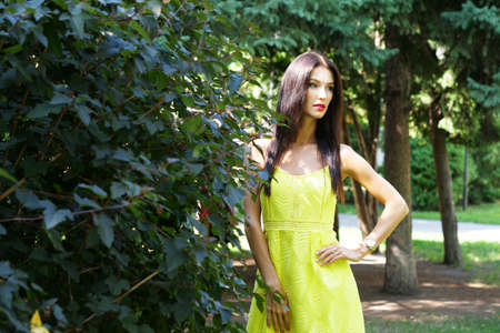 Waist up portrait of beautiful young woman in yellow dress standing in summer park and looking away.