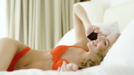 Young attractive woman in red lingerie talking on cell phone, lying in bed. Stock fotó