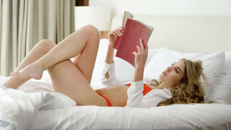 Attractive sensual girl in red underwear and white shirt lying in bed in a luxury bedroom and reading a magazine.