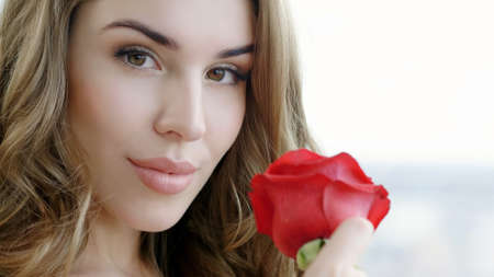 Portrait of an attractive blonde young woman with red rose looking at camera.