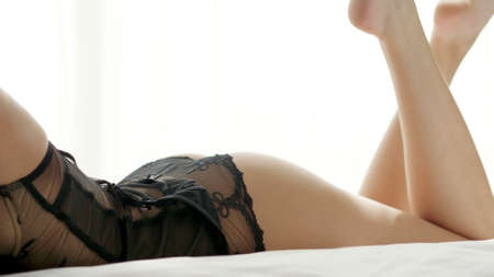 Young beautiful woman dressed in black lingerie lying in the bed in the bedroom.