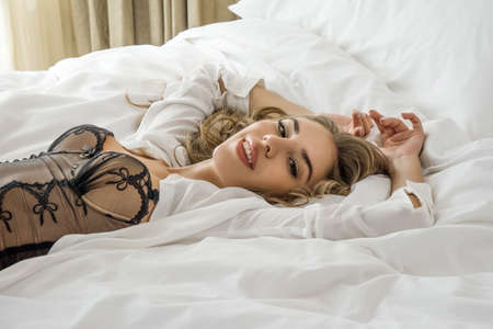 Young beautiful happy woman dressed in black lingerie lying in the bed in the bedroom and looking at camera.