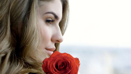 Beautiful girl in profile. Portrait of an attractive blonde young woman with red rose.