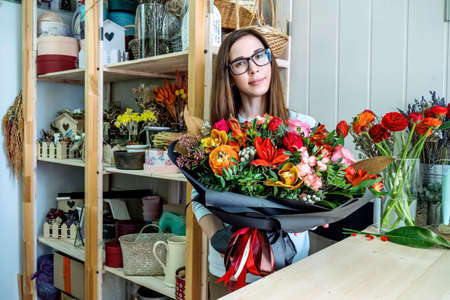 Female florist in flower shop. Woman holding in hands a beautiful and stylish bouquet of fresh flowers in floral design studio. Фото со стока