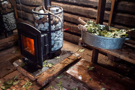 A traditional Russian sauna. Interior of a steam room. Wood-burning stove and oak brooms in bathhouse. Stock fotó