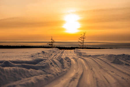Scenic winter landscape of sundown over snowy road across the frozen river Yenisei in Siberia.