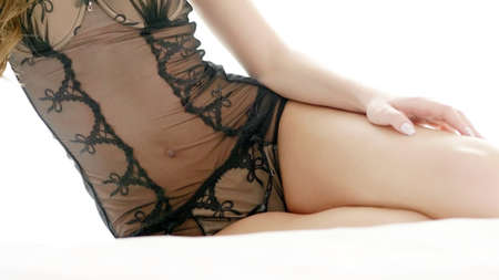 Young beautiful woman dressed in black lingerie sitting on bed in the bedroom.