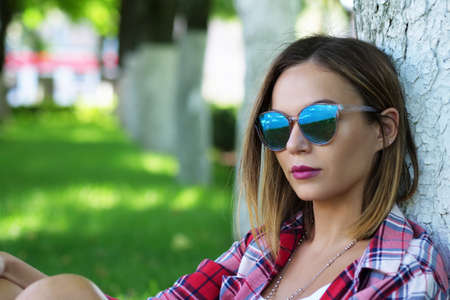 Portrait of beautiful young woman in sunglasses sitting under tree on green grass at city park. Фото со стока