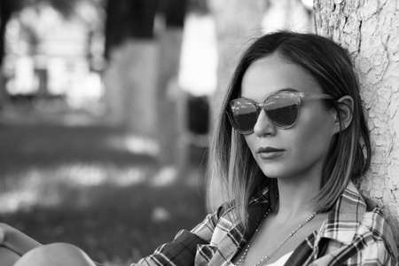 Portrait of beautiful young woman in sunglasses sitting under tree on green grass at city park. Stock fotó
