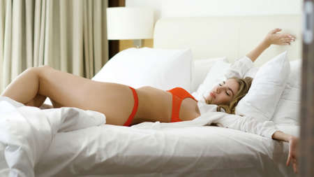 Beautiful young woman in red underwear and white shirt waking up from a deep sleep in her bedroom. Stock fotó