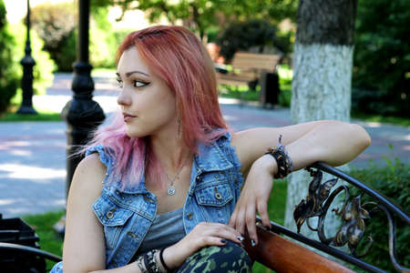 Punk or hipster woman with pink dyed hair resting on wooden bench in urban park.