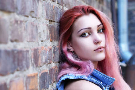 Teenage girl with pink hair sitting against brick wall in the background. Фото со стока