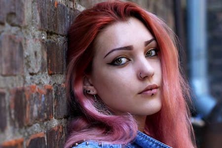 Young attractive hipster girl with pink hair and nose and lips piercing sitting against brick wall.
