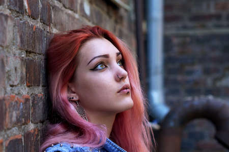 Teenage girl with pink hair sitting against brick wall in the background. Stock fotó