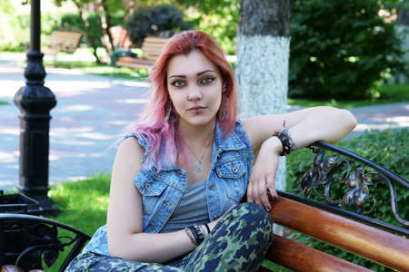 Beautiful punk or hipster young woman with pink hair sitting on park bench and looking at camera.