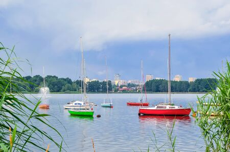 Boats on the water. Colorful boats on the urban lake with buildings in the background. Stock Photo