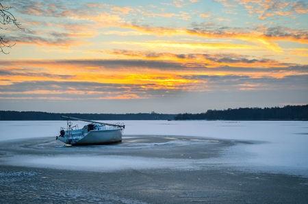Afternoon winter landscape. Boat on a frozen lake. Stock Photo