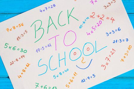 Creative idea depicting the return of children to school. White paper with mathematical operations and text back to school.