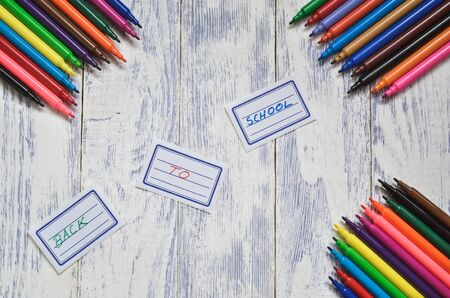 Creative concept with school supplies. Labels with back to school text and markers on a wooden desk.