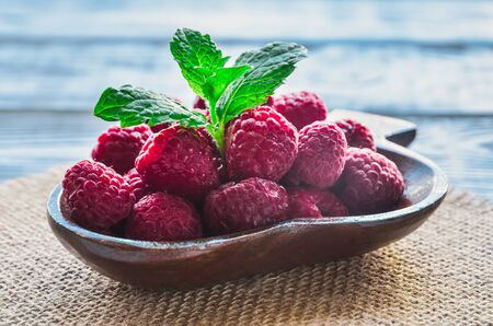 Fresh red fruits. Juicy raspberries in a wooden dish. Stockfoto