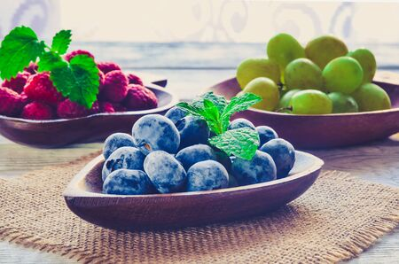 Fresh purple fruits. Juicy blueberries with other fruit in the background.