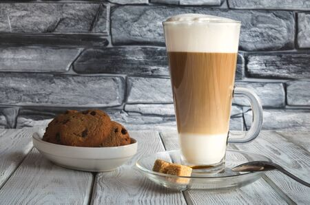 Delicious sweet breakfast. Coffee latte macchiato with cookies on a wooden table.