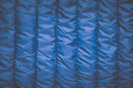 Shiny clothing background. Dark blue background from quilted material.