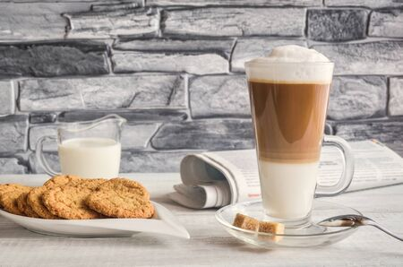 Conceptual delicious sweet breakfast. Latte macchiato coffee with oat cookies with and morning newspaper.