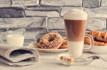 Conceptual delicious sweet breakfast. Latte macchiato coffee  with sweet donuts with a hole and morning newspaper.