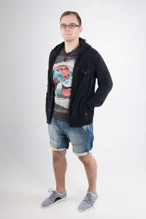 Young man in black hoodie and jeans isolated