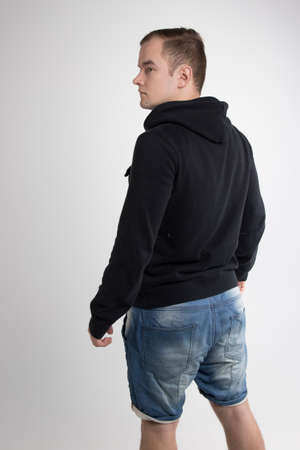 Young man standing back isolated