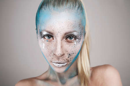 Beautiful blonde girl with bodyart on face isolated Фото со стока