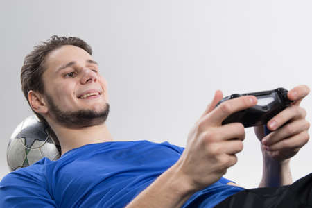 Young man playing video games in black shirt isolated Фото со стока