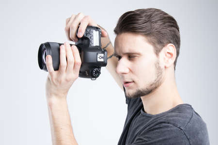 Young man holding camera in black shirt isolated