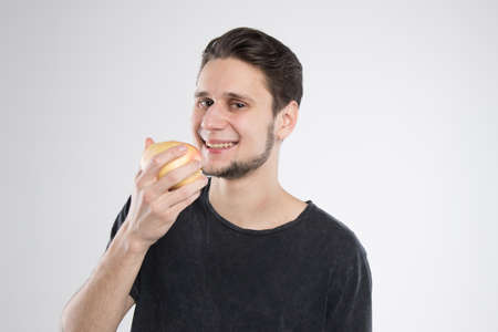 Young man eating apple in black shirt isolated