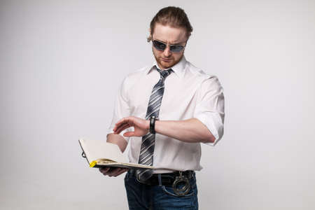 Portrait of young redhead man with beard white shirt and grey tie sunglasses isolated