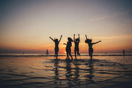 Beautiful party girls silhouette on sea. Happy people. Фото со стока - 142376802