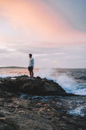 A man standing on a rocky beach. Man standing on rocks near the sea. Bursts of waves. Sunset