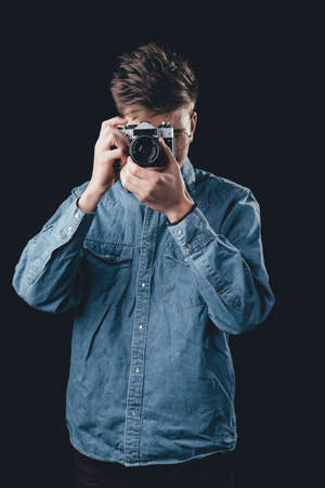 A man taking picture by old vintage camera. Man on dark background with camera. Фото со стока