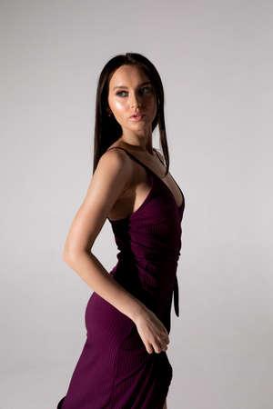 Studio photo of pretty brunette woman in trendy purple dress. Фото со стока
