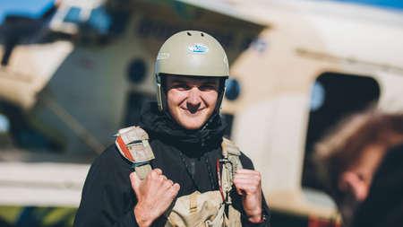 A man wearing a helmet with parachute after landing