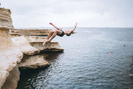 A man swimming in a body of water. Jumping from rock to the water with salto Фото со стока