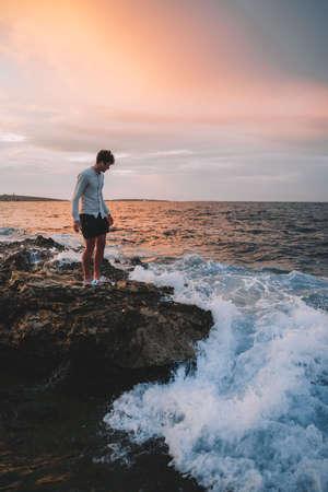 A man standing on a rocky beach