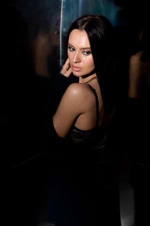 Studio photo of pretty brunette woman in twilight in bra looking over his shoulder