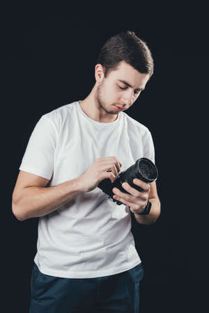 A man holding a camera. Man in white t-shirt on dark background.