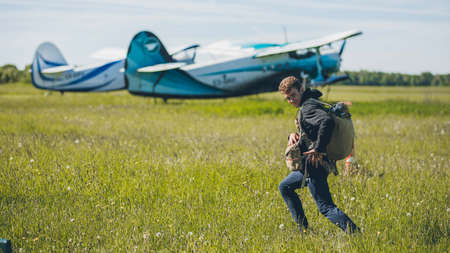 A man standing in front of a plane in the grass with parachute and in helm