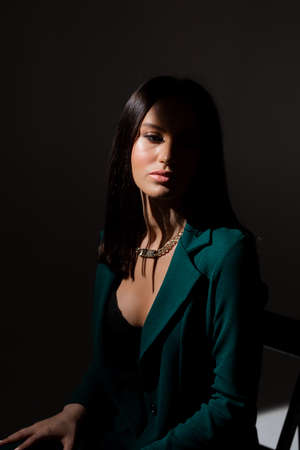Studio photo of pretty brunette woman in twilight sitting on black chair. A ray of light hits her face.