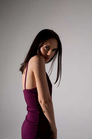Studio photo of pretty brunette woman in trendy purple dress. Looking to camera