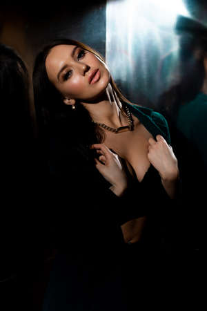 Studio photo of pretty brunette woman in twilight in bra posing to camera. Glossy background